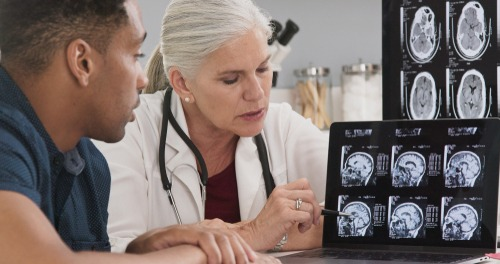 doctor analyzing scans of brain injury
